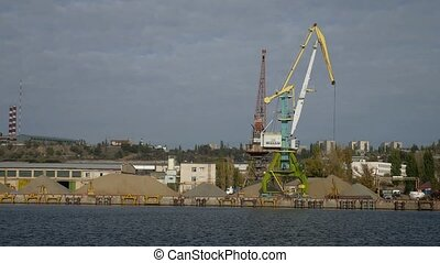 crane cargo in the river port view from sea to ship loading