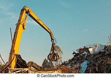 recycling center - crane claw on top of pile with scrap...