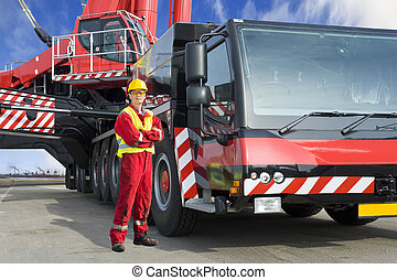 Crane driver, posing next to the huge mobile crane he's...