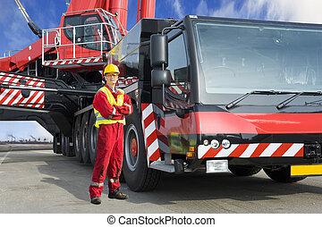 Crane driver, posing next to the huge mobile crane he's...
