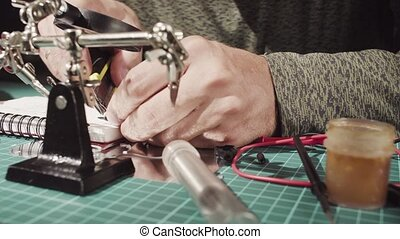 Male hands repairing wire for electronic devices. - Crane....