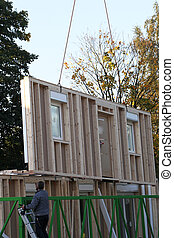 Crane hoisting up a prefabricated wall of a new build timber house from the trailer on which it has been delivered to the building site