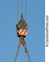 Crane hook over blue sky.