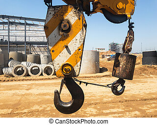 Crane hook with yellow stripes on the background of an empty construction site
