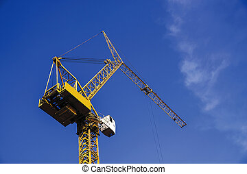 Crane in construction site with blue sky background