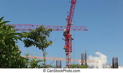 crane jib finishes turn above frame of skyscraper - crane...