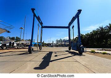 Crane lifting boats at harbor