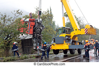 Crane lifting crashed truck - Yellow crane lifting a crashed...