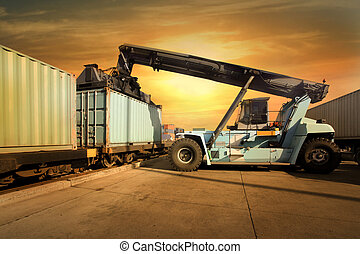 Crane lifting up container in sunset