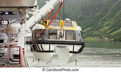 Crane lifts boat to huge liner, worker takes hook for hitch...