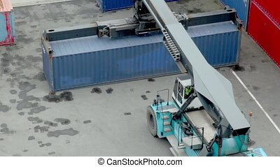 Crane lifts large weight container, view from above