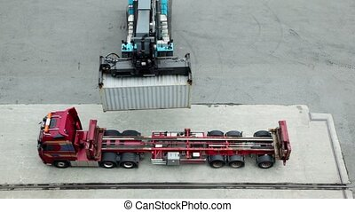 Crane moves and loads container to truck, view from above