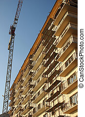 Crane next to building covered by scaffolds