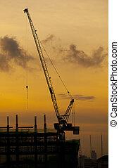 crane of building construction on dusky sky
