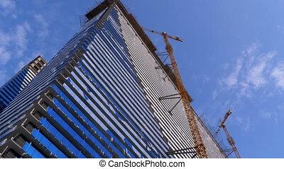 Crane on a Construction Site against the Blue Sky is Building New Skyscraper. Building Construction. The process of building a multi-storey modern residential skyscraper. Concrete panel building under construction. 4K. Batumi, Georgia