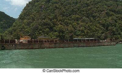 Handheld, medium wide shot of a crane on a docked barge.
