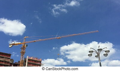 Crane on the background of a trace of the aircraft flying in the blue sky