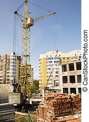 Crane on the construction site against blue sky