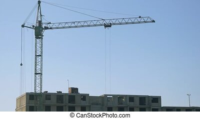 Crane on the construction site with workers by winter