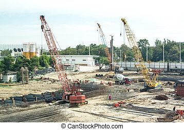 crane operating among metal foundation poles