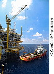 Crane operation on offshore construction platform. Cargo being loaded from a offshore platform onto a supply vessel.