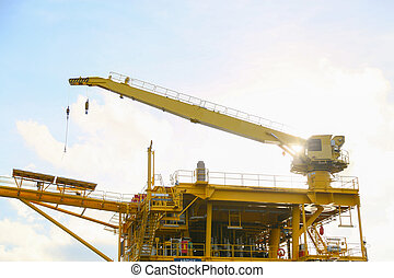 Crane operation transfer cargo on the platform and moving cargo from supply boat, heavy lift in oil and gas construction platform.