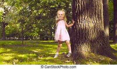 A little girl playing in a park on the grass near the tree