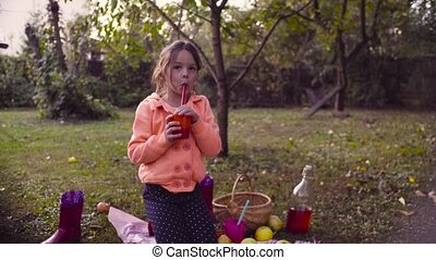 Picnic in the garden. A girl sitting on grass and drinking compot