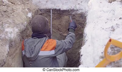 Ecologist measuring roulette depth of a soil slit - Crane...