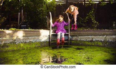 Little girl sitting on a metal ladder and dangling feet in...