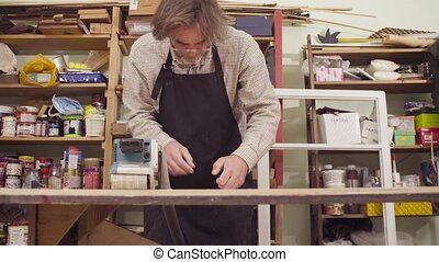 Man is polishing wood with a machine for grinding - Crane...