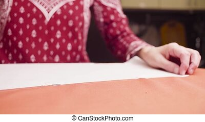 Middle-age woman hands pinning a paper pattern to the fabric...