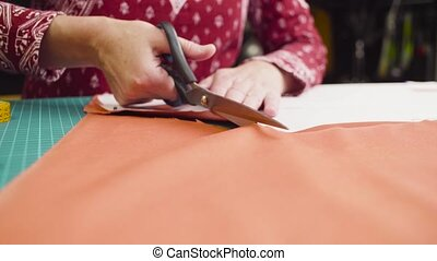 Middle-age woman hands with scissors cutting fabric - Crane...