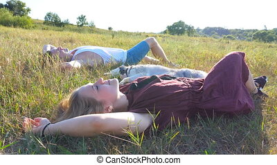 Crane shot of young couple in love lying on green grass at field and stroking their siberian husky dog at sunny day. Happy pair relaxing and enjoying summer weekend at sunset. Side view Close up