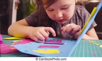 Little girl glueing colored paper - Crane shot....