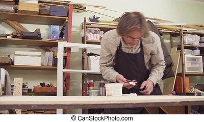 Senior carpenter spackling wooden board - Crane shot. Senior...