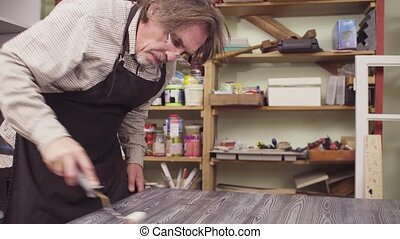 Senior man covering painted wooden surface with a varnish -...