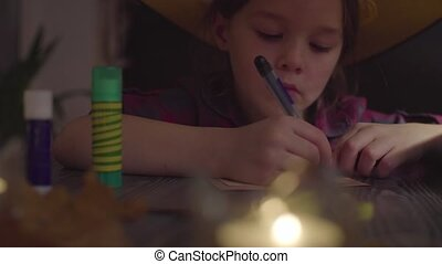 The girl drawing spider web on a card. Preparing for the celebration of Halloween