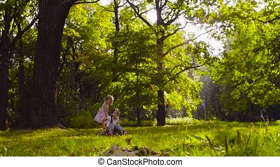 Three girls playing in the park on the grass among the trees...