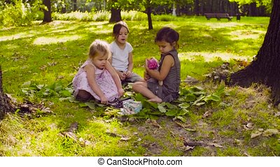 Three girls sitting in the park on the grass near the tree -...