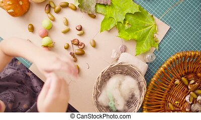 Little girl sitting at the desk makes necklace of acorns -...