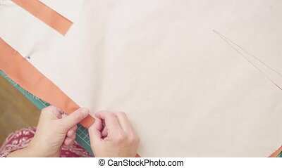 Middle-age woman hands drawing outline of a paper pattern...