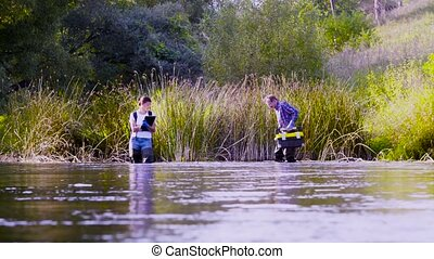 Two scientists ecologists in high rubber boots walking in...