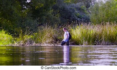 Woman ecologist in high rubber boots walking in the water of...