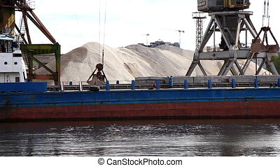 Crane unload gravel from barge on river