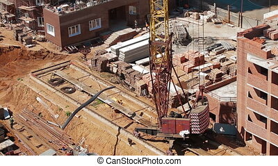 Crane unloads metal from truck. construction site