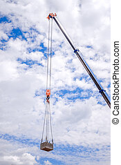 Crane with a cargo with a blue sky background