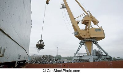 Crane with magnet carrying heap of garbage on disposal dump...