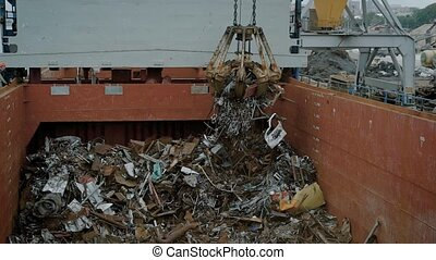 Crane with magnet in process of dumping trash in container -...