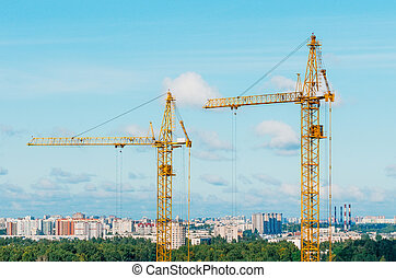 Cranes and housing estate against the background of the city and clouds sky.